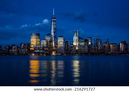 New York City Manhattan downtown skyline with skyscrapers illuminated over Hudson River panorama, including the One World Trade Center