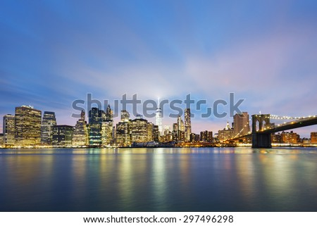 New York City Manhattan midtown at dusk with skyscrapers illuminated over east river - stock photo