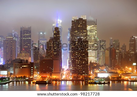 New York City Manhattan midtown 42nd street skyline at night with skyscrapers over Hudson River viewed from New Jersey. - stock photo