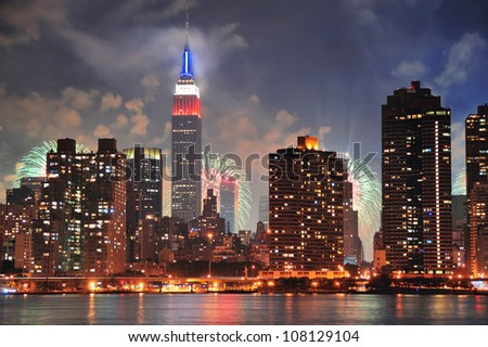 New York City Manhattan midtown panorama at dusk with skyscrapers illuminated over east river - stock photo