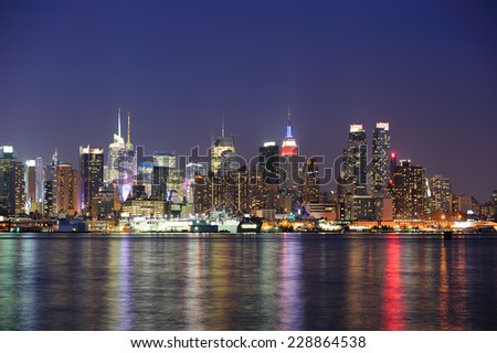 New York City Manhattan midtown skyline at night with lights reflection over Hudson River viewed from New Jersey Weehawken waterfront. - stock photo
