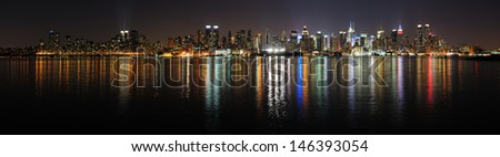 New York City Manhattan midtown skyline panorama at night with lights reflection over Hudson River. - stock photo