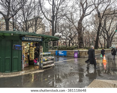 New York City,Manhattan News stand on Union Square during rain storm 2/16/2016, 12:31:58 PM with people walking in rain - stock photo