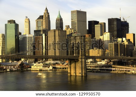 New York City Manhattan with Brooklyn Bridge and skyscrapers over Hudson River in the morning. - stock photo