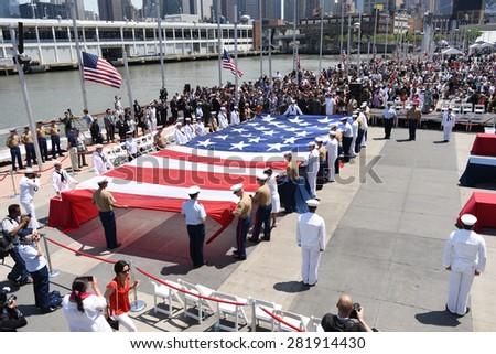 NEW YORK CITY - 25 MAY 2015: Mayor Bill de Blasio & Gen John Kelly presided over Memorial Day observances on Pier 86 by the USS Intrepid. Unfurling enormous US flag - stock photo