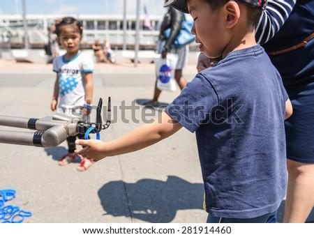NEW YORK CITY - 25 MAY 2015: Mayor Bill de Blasio & Gen John Kelly presided over Memorial Day observances on Pier 86 by the USS Intrepid. Kids explore Navy robotics - stock photo