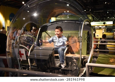 NEW YORK CITY - MAY 25 2015: Mayor de Blasio & General John Kelly led Memorial Day commemorations on Pier 86 by the USS Intrepid. Boy in helicopter on hangar deck of USS Intrepid - stock photo