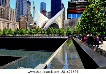 New York City - May 23, 2015:  9/11 Memorial north tower footprint with cascading waterfalls and the rising Santiago Calatrava PATH Transportation Center with its distinctive soaring white wings  * - stock photo
