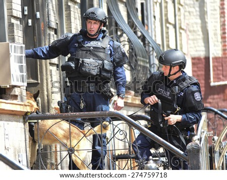 NEW YORK CITY - MAY 1 2015: NYPD emergency services, K9 & helicopter patrol search a closed off a block in Sunset Park, Brooklyn, for a robbery suspect. K9 & officers entering apartment building - stock photo