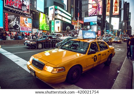 NEW YORK CITY - MAY 12: Yellow cab on Times Square traffic and animated LED signs, is a symbol of New York City and the United States, May 12, 2016 in Manhattan, New York City. USA.