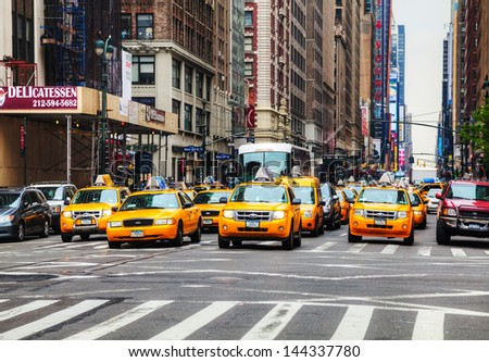 NEW YORK CITY - MAY 11: Yellow taxis at the street on May 11, 2013 in New York. Yellow cars serve as taxis in NYC and are easy to spot among other vehicles because of their color.