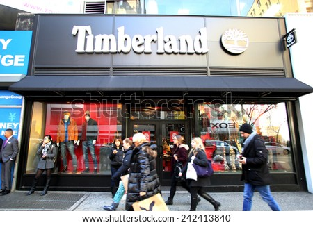NEW YORK CITY - MONDAY, DEC. 29, 2014: Pedestrians walk past a Timberland shoe anc clothing store.  Timberland LLC is an American manufacturer and retailer of outdoors wear with a focus on footwear - stock photo
