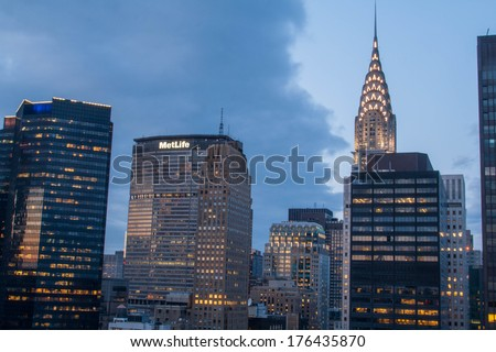 NEW YORK CITY, NEW YORK - MARCH 29, 2013: The lights come on as the sun goes down behind the famous Chrysler building in Manhattan. - stock photo