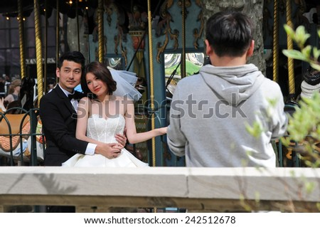 NEW YORK CITY, NEW YORK - MAY 1, 2014: Asian couple poses for photos in Bryant Park, location of the NY Public Library. Many modern Asian couples have elaborate photos taken before their weddings.