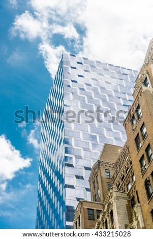 NEW YORK CITY, NEW YORK, USA MAY 23, 2013: mirror modern building in contrast to a classic brick building in New york - stock photo