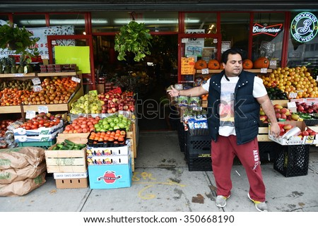 NEW YORK CITY - NOV 11: A man sell fruit at a supermarket store in Queens on Nov 11, 2015 in New York City, USA. - stock photo