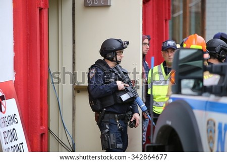 NEW YORK CITY - NOVEMBER 22 2015: Emergency response personnel staged an active shooter exercise in Manhattan's Lower East Side. Counter terrorism officer in tactical gear with fake assault rifle