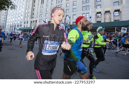 NEW YORK CITY - NOVEMBER 2 2014: the 43rd annual New York City Marathon saw more than 50,000 entrants run through all five boroughs. Array of runners approach finish line along 59th Street