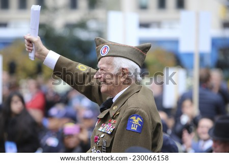 NEW YORK CITY - NOVEMBER 11 2014: the 95th annual Veteran's Day parade along Fifth Avenue is the largest Nov 11 celebration in the United States. World War ii veteran stands at Madison Square Park - stock photo