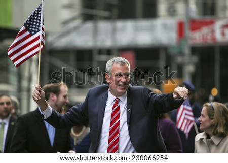 NEW YORK CITY - NOVEMBER 11 2014: the 95th annual Veteran's Day parade along Fifth Avenue is the largest Nov 11 celebration in the United States. NYC Mayor Bill De Blasio with US flag - stock photo