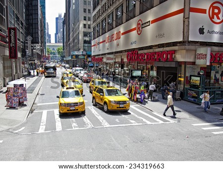New York City, NY - June 28, 2014:  Intersection in Times Square with taxi cabs, pedestrians and store fronts in New York City, NY on June 28, 2014.