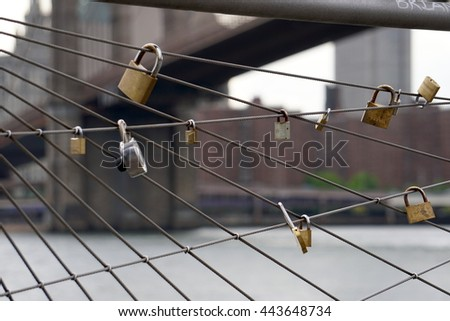 New York City, NY - June 7, 2016: Love locks hang in DUMBO park along the East River with the Brooklyn Bridge in the background