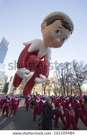 NEW YORK CITY, NY - NOVEMBER 28 : Elf on the Shelf balloon flying through W 59th ST during the Macy's 87th Annual Thanksgiving Day Parade on November 28, 2013 in New York City, New York.  - stock photo