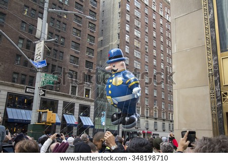 NEW YORK CITY, NY - NOVEMBER 26: NYPD officer balloon flying between buildings in city street during the 89th Annual Macy's Thanksgiving Day Parade on November 26, 2015 in New York City. - stock photo