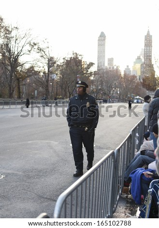 NEW YORK CITY, NY - NOVEMBER 28 : Young NYC Officer walking W 59th ST piror to the Macy's 87th Annual Thanksgiving Day Parade on November 28, 2013 in New York City, New York.  - stock photo