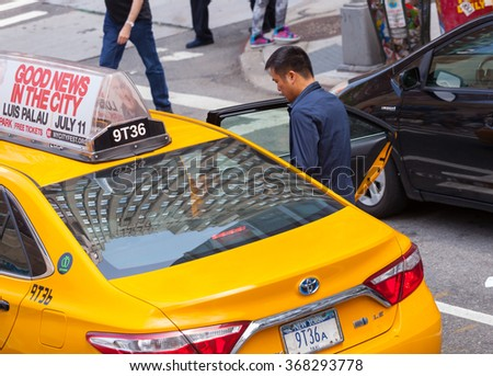 NEW YORK CITY, NY, USA - JULY 07, 2015: Asian tourist takes the yellow cab in Manhattan, NYC. The taxicabs of New York City are widely recognized icons of the city. - stock photo