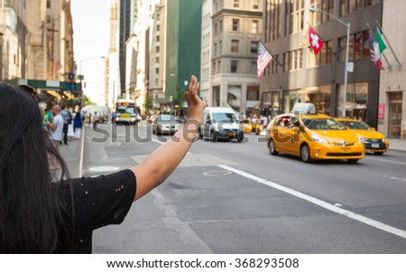NEW YORK CITY, NY, USA - JULY 07, 2015: Tourist call a yellow cab in Manhattan with typical gesture with arm up. The taxicabs of New York City are widely recognized icons of the city. - stock photo