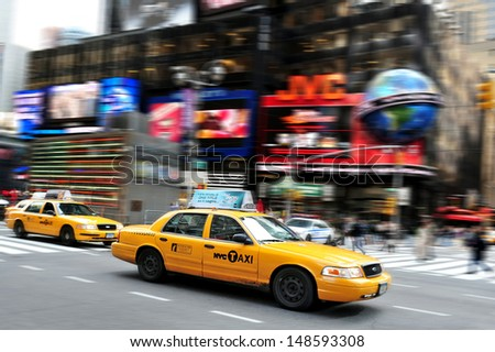 NEW YORK CITY - OCT 15 2010:New York City yellow taxi cabs race through Time Square.It's one of the world's busiest pedestrian intersections and a major center of the world's entertainment industry. - stock photo