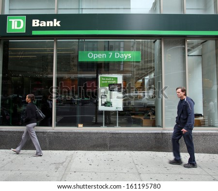 NEW YORK CITY - OCT 23 2013:  Pedestrians walk past a branch office of TD Bank, N.A.,  in Manhattan on Wednesday, October 23, 2013.  - stock photo