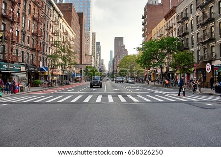 NEW YORK CITY - OCTOBER 03, 2016: Long view up 1st Avenue whith people crossing the street with almost no car traffic