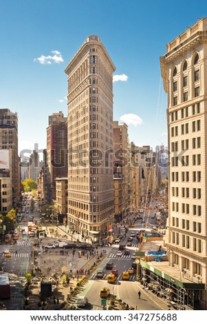 NEW YORK CITY - OCTOBER  17, 2015: View of midtown Manhattan along Broadway at the historic Flatiron Building with cars and people visible from a distance.   - stock photo