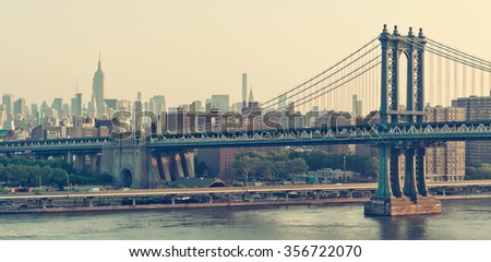 New York City panorama with the historic Manhattan Bridge suspension bridge crossing the East River at sunrise with a colorful orange sky - stock photo