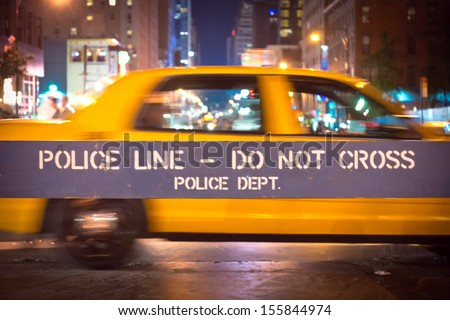 New York City police blue barricade to control traffic, with yellow taxi in background - stock photo