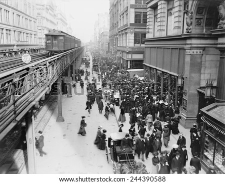 New York City's Sixth Avenue crowded with shoppers in 1903. Horse drawn carriages and wagons travel on the street level as an elevated train passes above. - stock photo