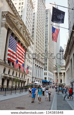 NEW YORK CITY - SEP 3: People walk in front of the New York Stock Exchange on Wall Street on September 3, 2011 in New York City. The NYSE is one of the most important stock exchanges worldwide. - stock photo