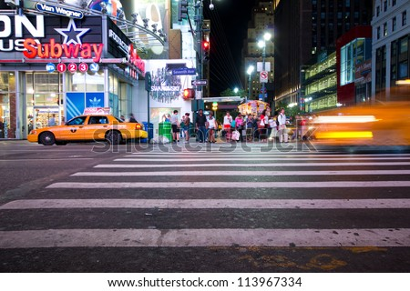 NEW YORK CITY - SEPT 13: Busy Manhattan crosswalk at 34th St. on night of Sept 13, 2012. This major street is home to The Empire State Building, Penn Station and Macy's Herald Square. - stock photo