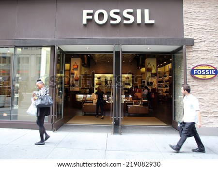 NEW YORK CITY - SEPT. 11, 2014: Pedestrians walk past a Fossil clothing and accessories retail store. Fossil, Inc. is an American designer and manufacturer of clothing and accessories - stock photo