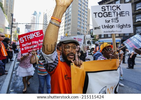 NEW YORK CITY - SEPTEMBER 4 2014: fast food workers and their supporters marched along 8th Ave calling for an increase in the minimum wage.Some attempted to block the street leading to several arrests - stock photo