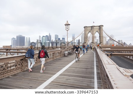 New York City, 13 september 2015: people engaged in bike run and others walking on brooklyn bridge new york with manhattan in the background