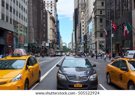 NEW YORK CITY - SEPTEMBER 24, 2016: Two yellow cabs and a dark Toyota are stopped for red light on 5th Avenue on Manhattan