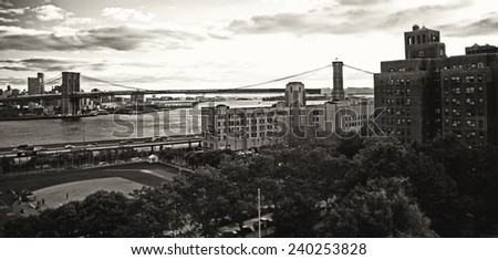 NEW YORK CITY - SEPTEMBER 22: View of the Booklyn bridge, river, baseball field and buildings from the Manhattan bridge in black and white. Taken on September 22, 2013 in New York City, NY. - stock photo