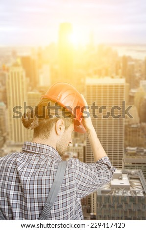 New York City skyline aerial view. worker with helmet watching the town from his place of work on a building roof - stock photo