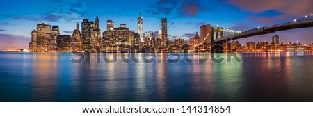 New York City skyline at night with Brooklyn Bridge - stock photo