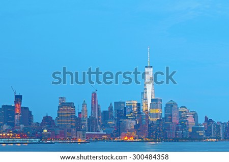 New York City skyline at sunset with illuminated business buildings - stock photo