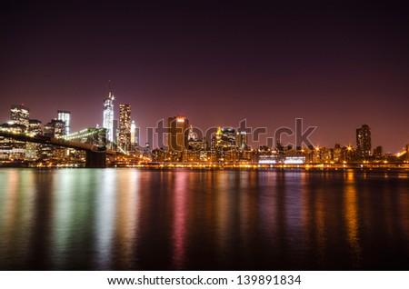 New York City skyline by night. Manhattan and Brooklyn Bridge breathtaking view. - stock photo