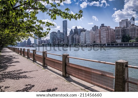 New york city skyline of midtown Manhattan and a path with a tree - stock photo